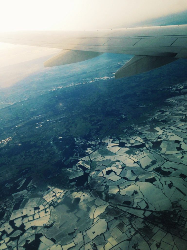 The view across snowy fields from an aeroplane window - How to Travel Cheap in Europe!
