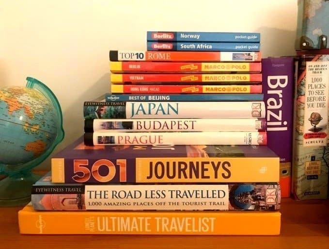 A stack of travel books and travel guides - Travel related things to do at home during lockdown!